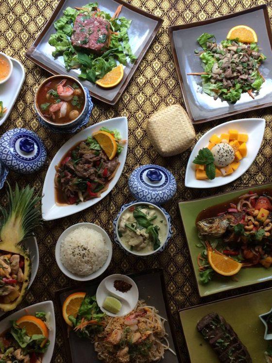 Jolie table avec plein de plats de cuisine thaïlandaise.